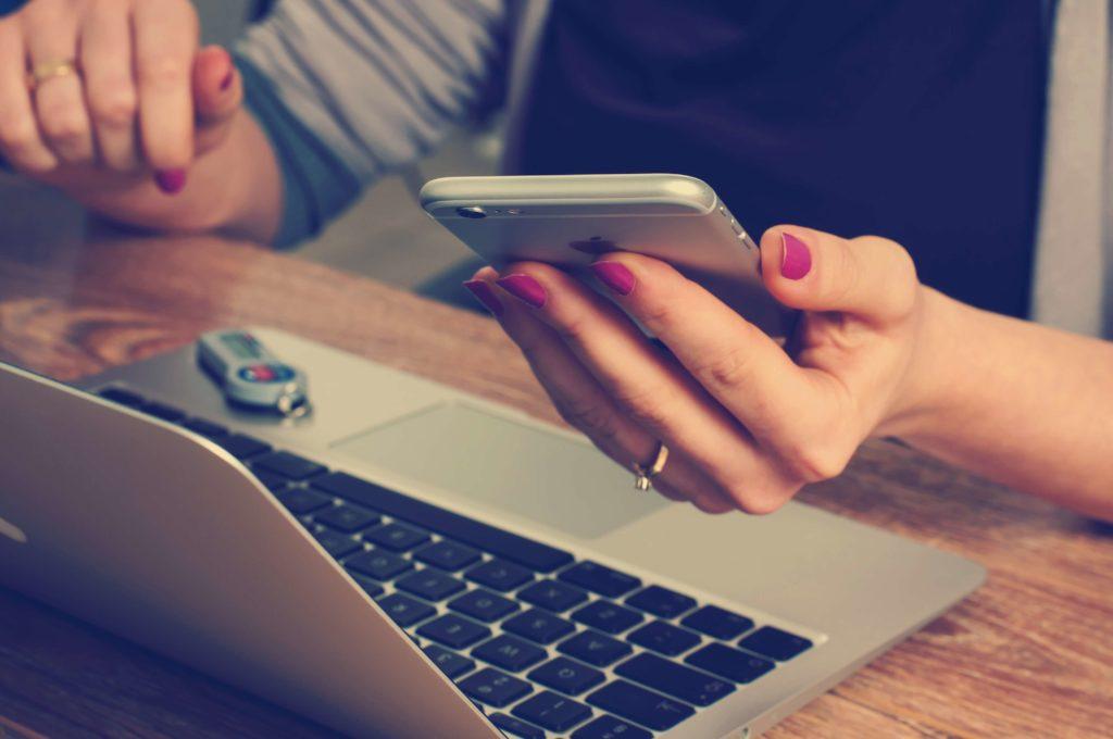 Smartphone und Laptop benutzt von weiblichen Händen