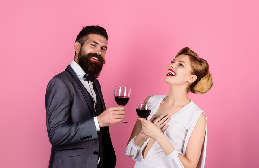 Ein lächelndes Paar mit einem Becher Wein