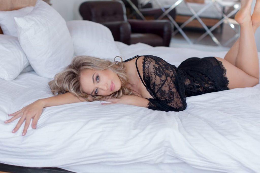 Blonde reife Frau liegt auf dem Bett