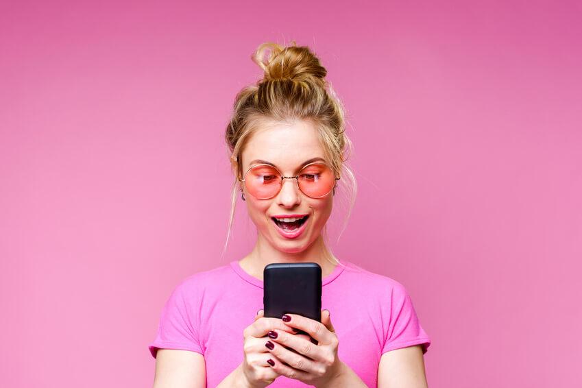 Junge Frau benutzt spirituelle Partnerbörse auf dem Handy
