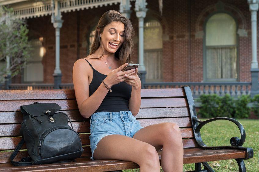 Junge Dame erhält eine nette Nachricht über eine Dating-App