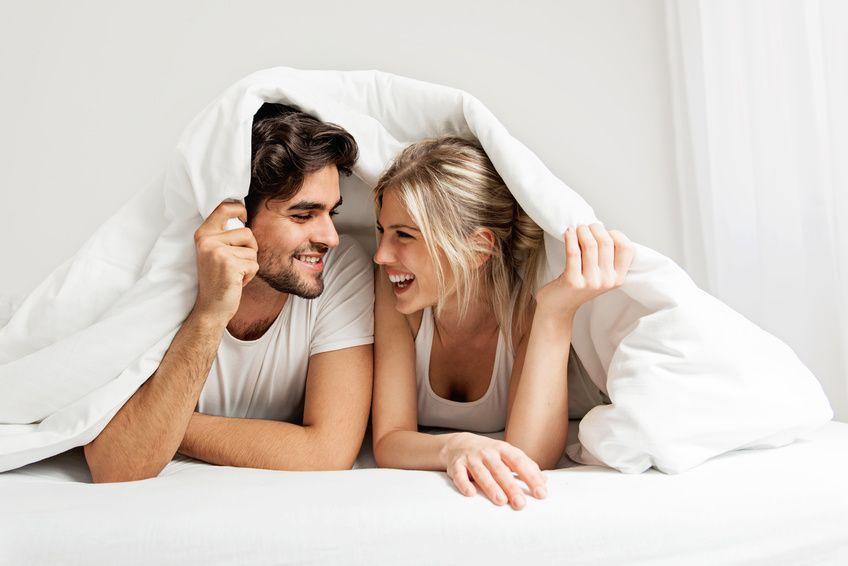 Christliches Paar lächelt unter dem Bettlaken