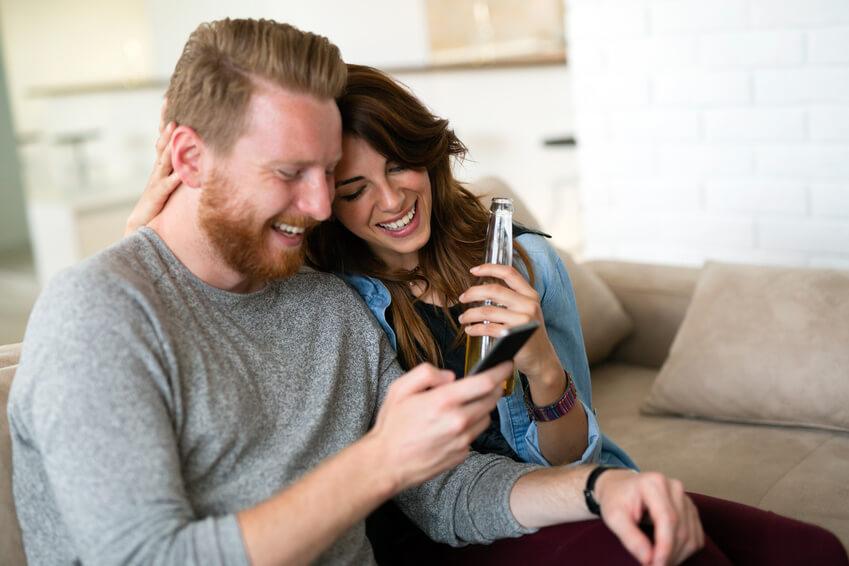 Gut aussehendes Paar chillt im Wohnzimmer und nutzt gemeinsam ein Smartphone