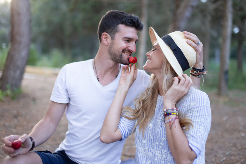 Süßes Paar teilt sich Erdbeeren im Wald
