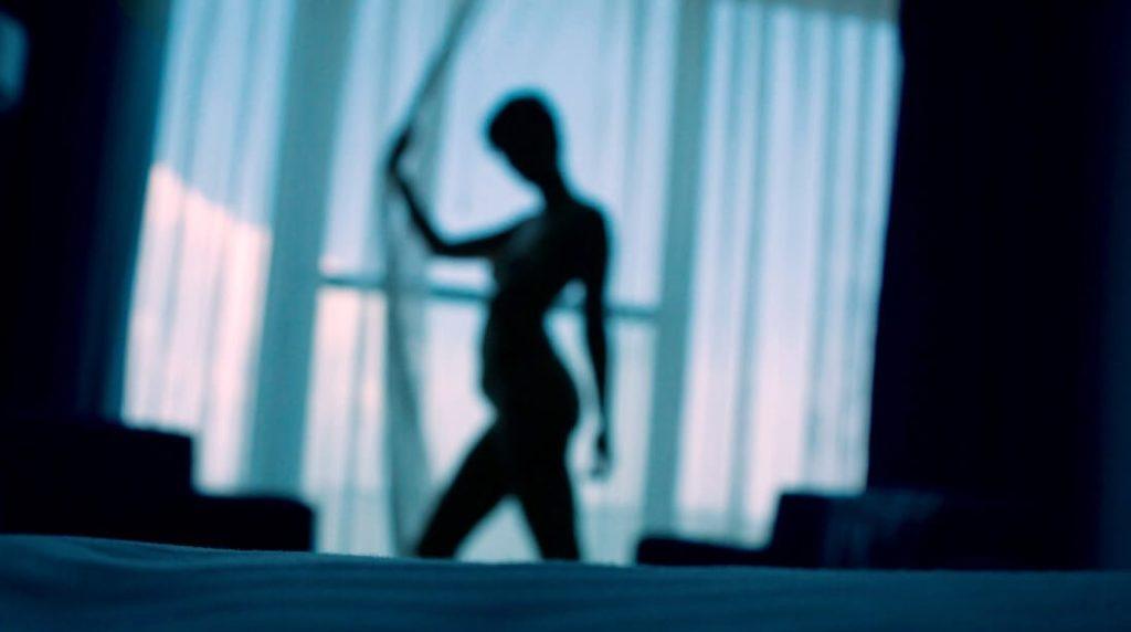 Nackte Frau vor grauem Vorhang in dunklem Setting