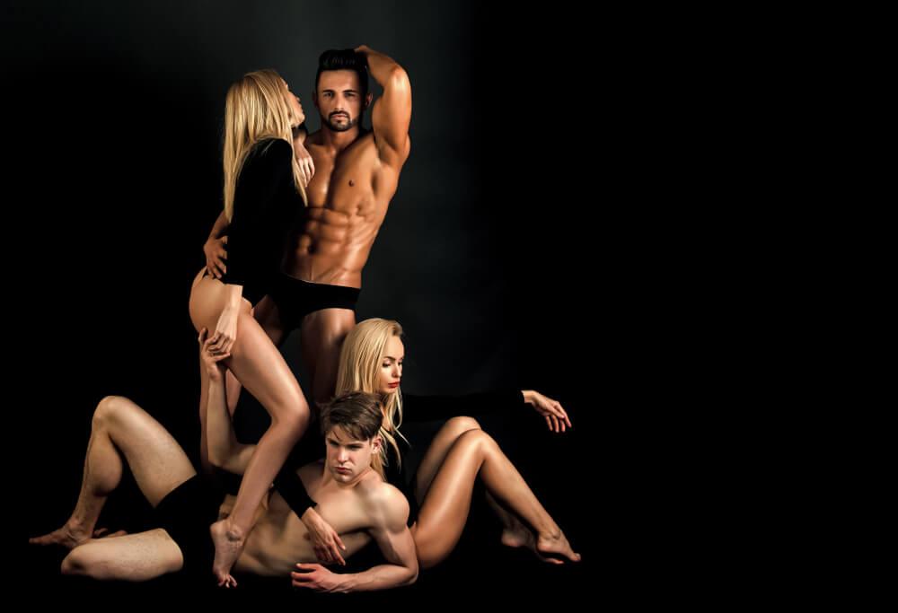 Zwei blonde Frauen und zwei dunkelhaarige Männer posieren zusammen und bereiten sich auf eine Swinger-Party vor.