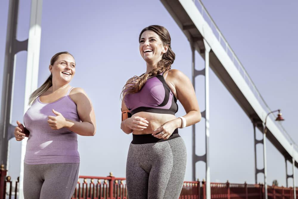 Zwei kurvige Frauen in ihrer Sportkleidung, die unter der Brücke durchlaufen