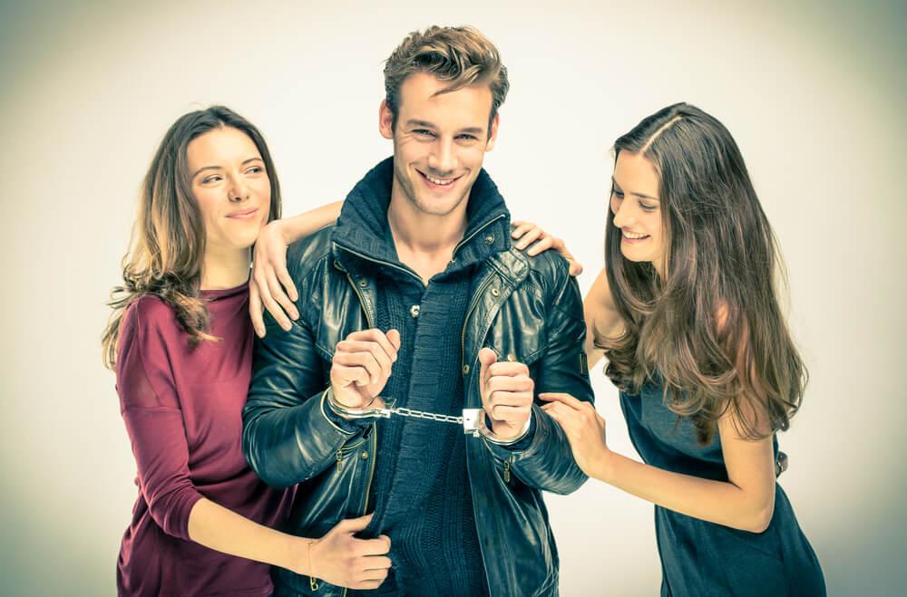Zwei gut aussehende Frauen mit einem heißen Kerl in Handschellen. Drei von ihnen lächeln alle.