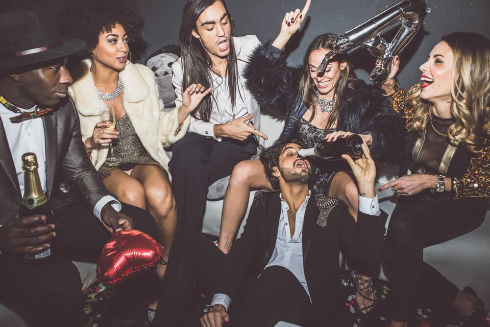 Sechs gutaussehende Männer und Frauen feiern eine lustige Party