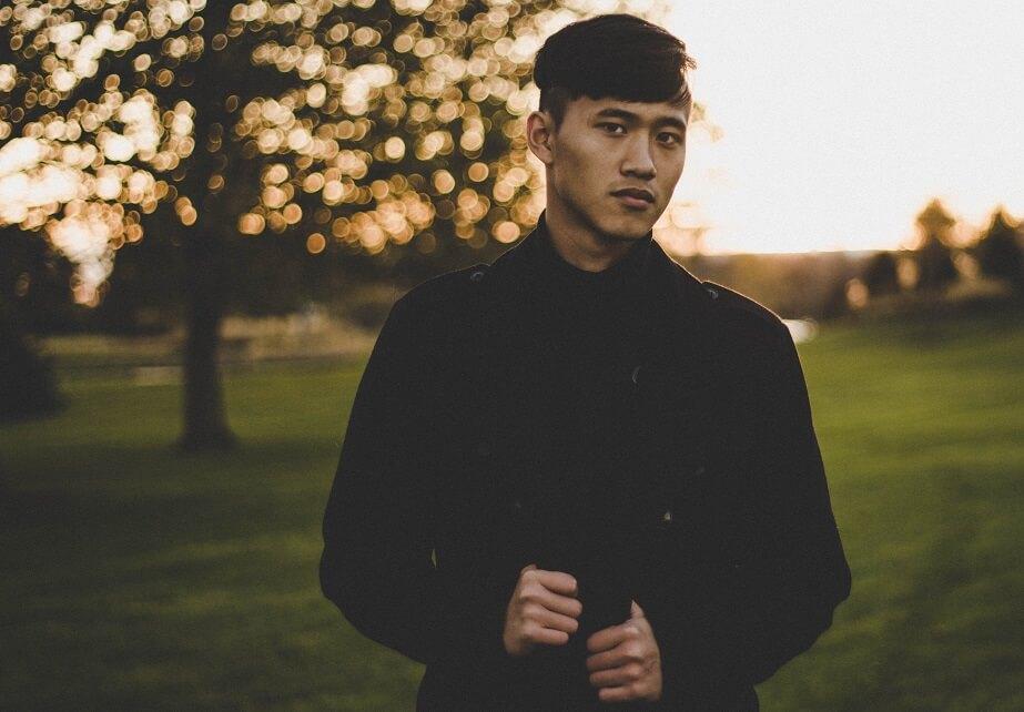 gut aussehender asiatischer Typ, der posiert und ernst in die Kamera schaut