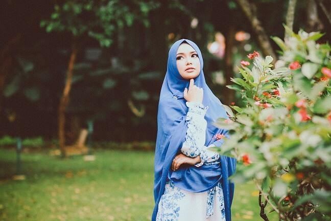 muslimisches Mädchen, das in einem Park etwas in blauer Kleidung betrachtet