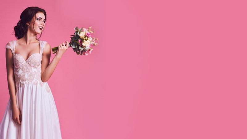 bestellte Braut im Hochzeitskleid zeigt ihren Brautstrauß