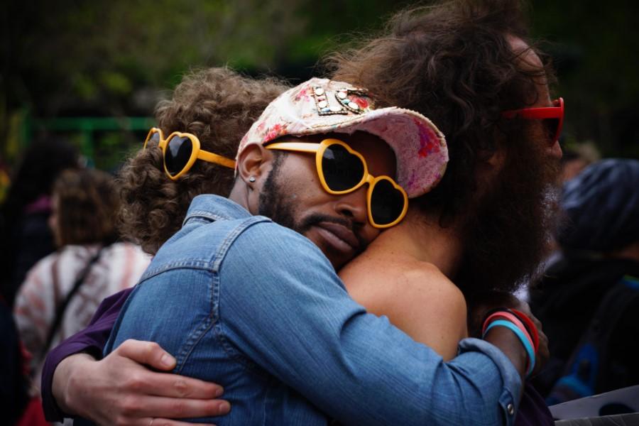 Demonstranten mit Herzsonnenbrille umarmen sich