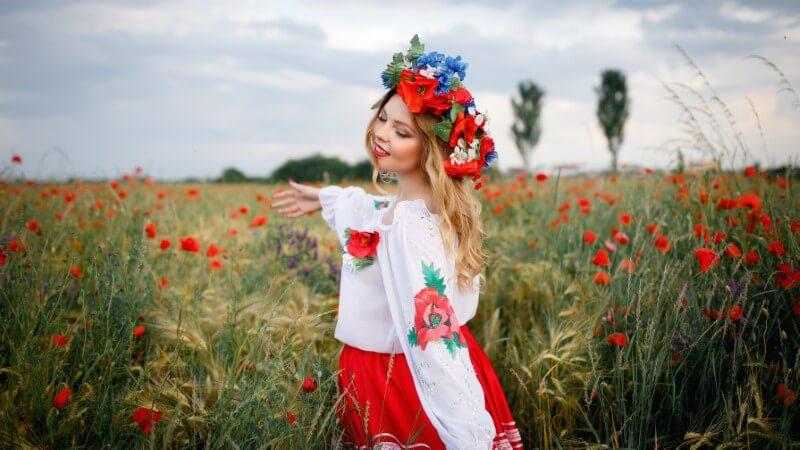 Schöne ukrainische Frau in traditioneller Kleidung mit Blumenkrohne in einem Mohnfeld