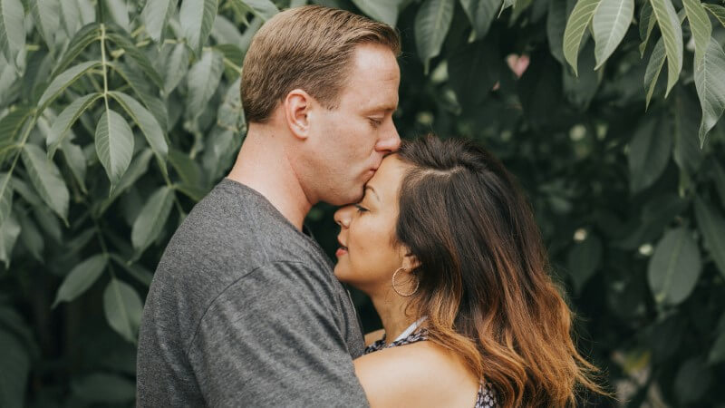 Mann in den Mittvierzigern gibt seinem attraktiven Date einen Kuss auf die Stirn.