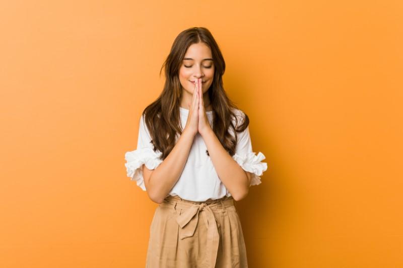 christliche frau faltet die hände zum beten