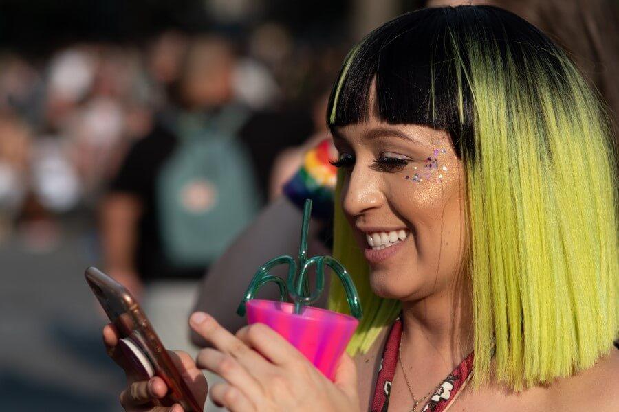 Junge Frau mit bunten Haaren hält ihr Smartphone und einen bunten Becher in der Hand