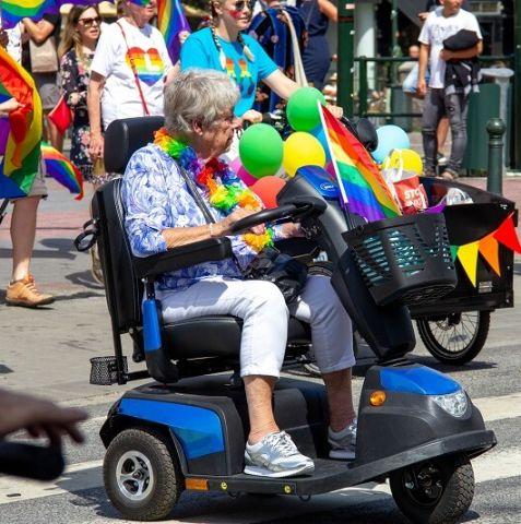 Eine ältere Frau in einer motorisierten Mobilitätshilfe trägt Regenbogenblumen in einer Pride-Parade.