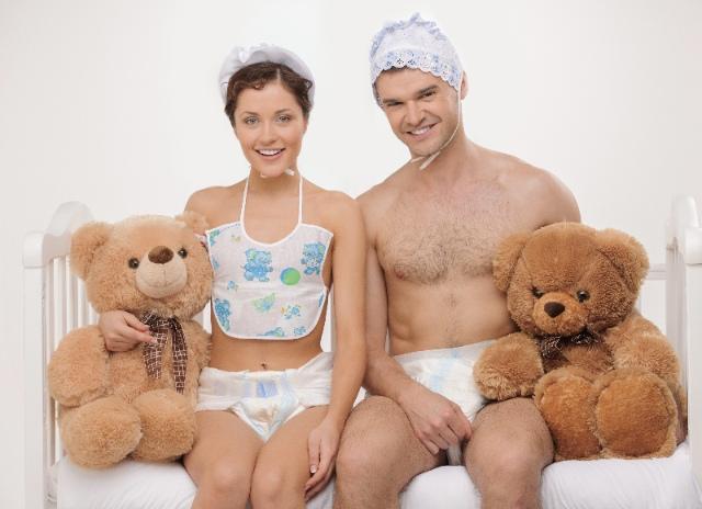 Ein Paar in Windeln sitzt auf einem Babybett mit zwei Kuschelbären