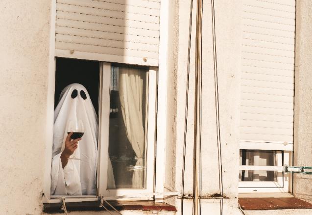 Geist mit einem Glas Rotwein in der Hand schaut aus dem Fenster