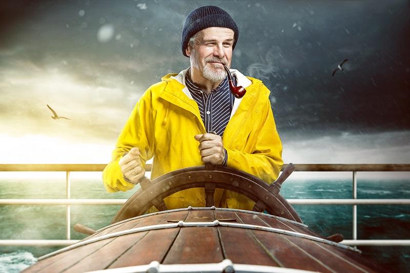 Charmanter Kapitän zur See steuert sein Schiff