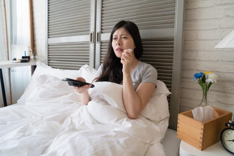 Weinende Frau im Bett und einer Fernbedienung in der Hand.