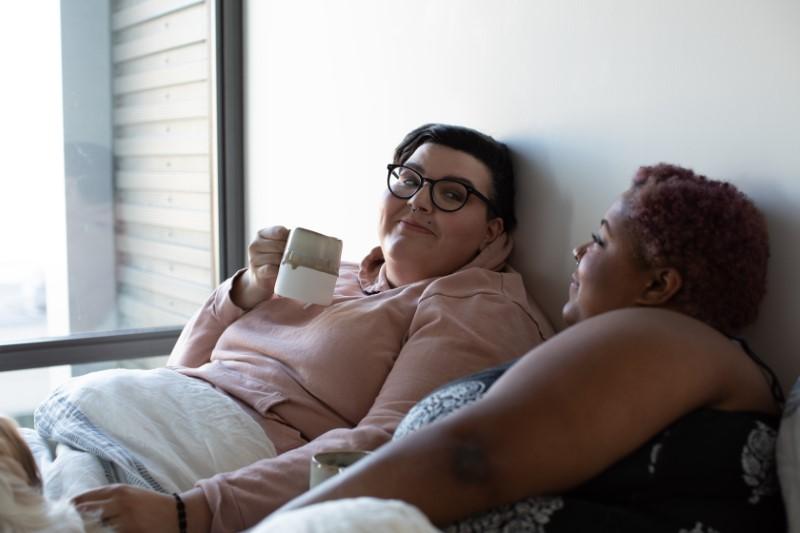 Lesbisches Paar im Bett mit einer Tasse Kaffee