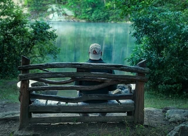 Single Mann wartet sitzend auf einer Bank