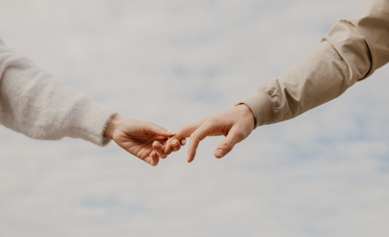 zwei Personen, die sich an der Hand nehmen