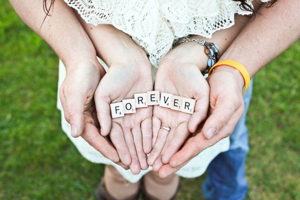 """Paar, das gemeinsam die Worte """"für immer"""" in den Händen hält."""