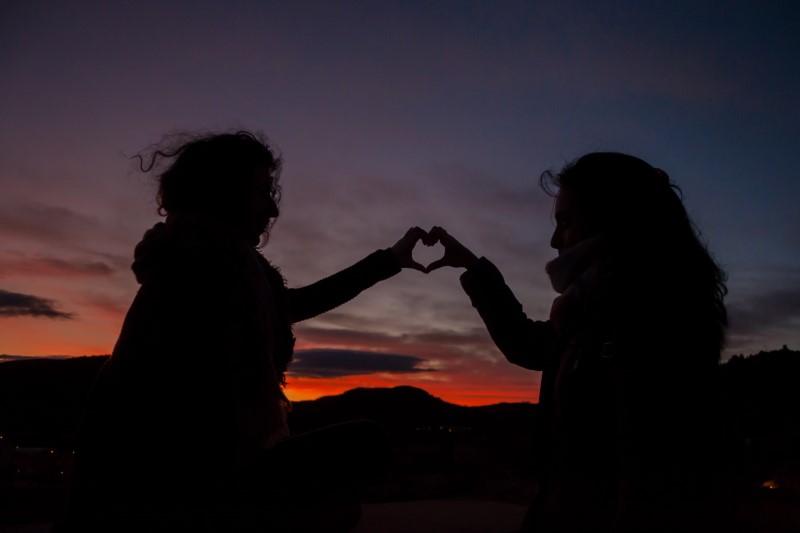 zwei Menschen, die im Sonnenuntergang mit ihren Händen ein Herz bilden