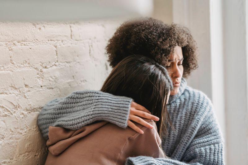 Frau tröstet Freundin die sich in einer toxischen Beziehung befindet