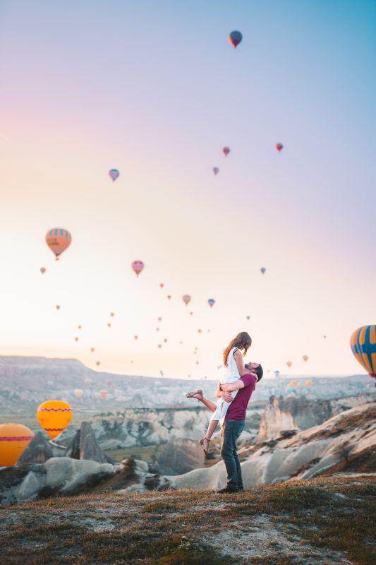 Paar feiert ihre Beziehung mit Luftballons im Hintergrund