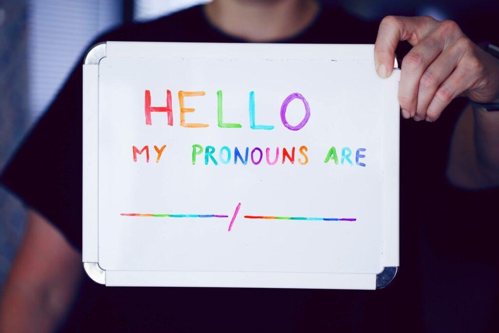 """jemand hält eine Tafel hoch, auf der steht """"Hallo, meine Pronomen sind keine"""""""