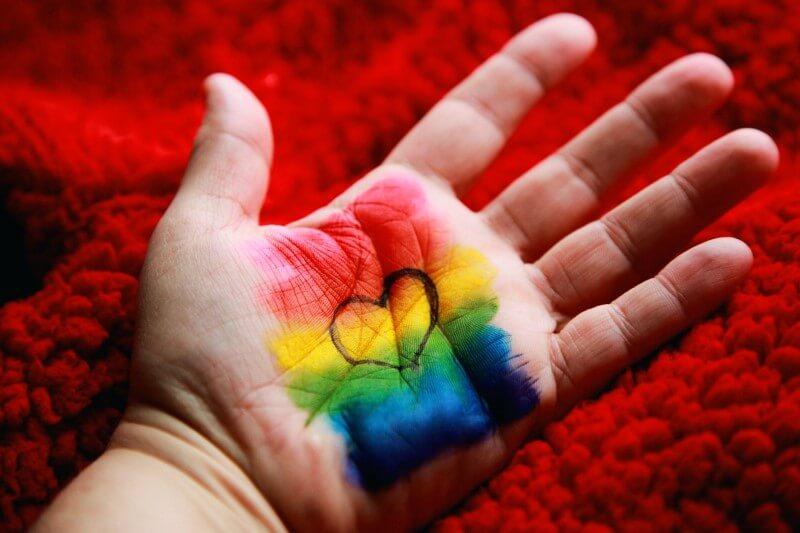 Handfläche mit LGBTQ+ Pride-Flagge und einem Herz