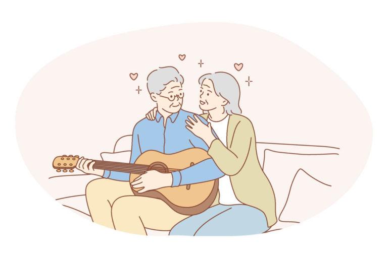 älteres Paar, das auf einem Sofa sitzt, sie umarmt ihn von hinten während er die Gitarre spielt