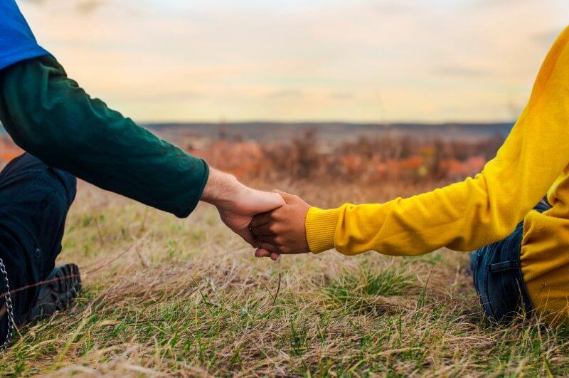 zwei Menschen sitzen im Gras und halten sich an den Händen