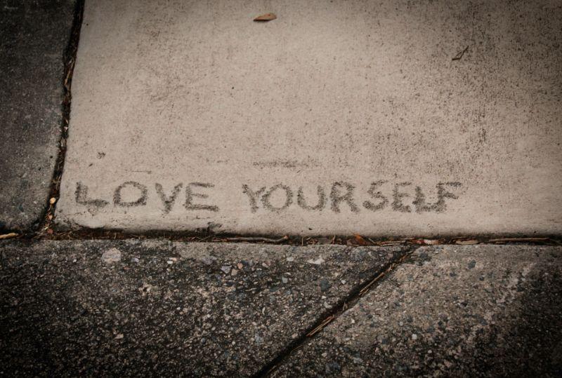 Liebe dich selbst auf einem Bürgersteig geschrieben