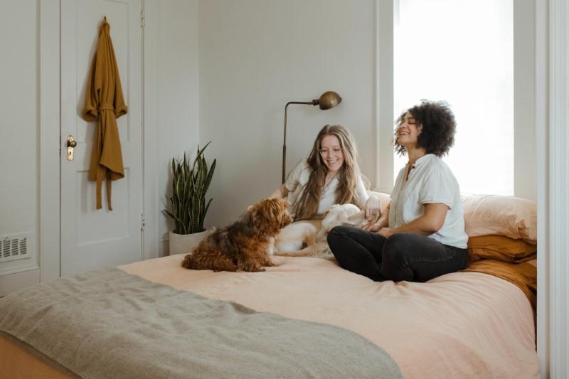 zwei Freundinnen sitzen mit ihren Hunden auf dem Bett