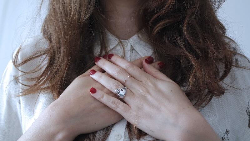 Frau hält Hände über ihr Herz