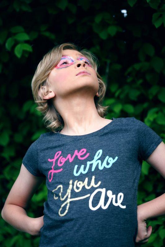 """Frau mit T-Shirt auf dem """"Liebe wer du bist"""" steht"""